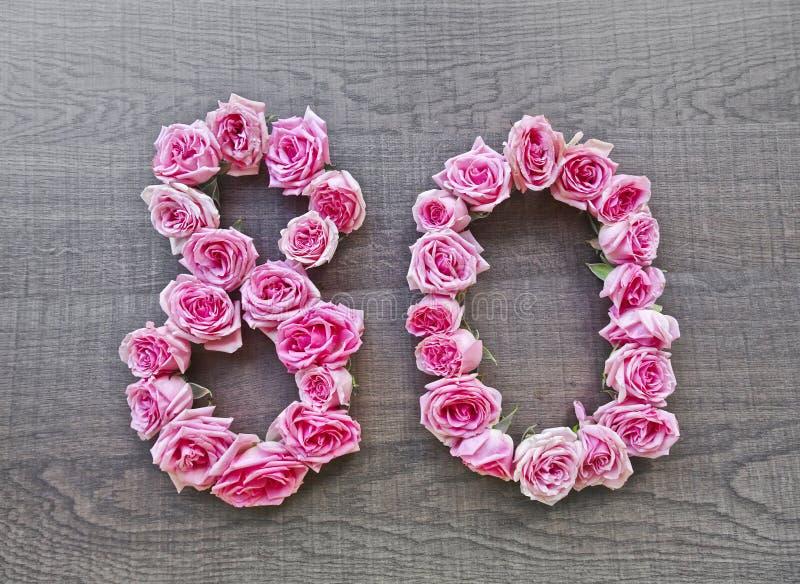80 achtzig - Weinlesezahl von rosa Rosen auf dem Hintergrund dunklen wood5 stockbilder