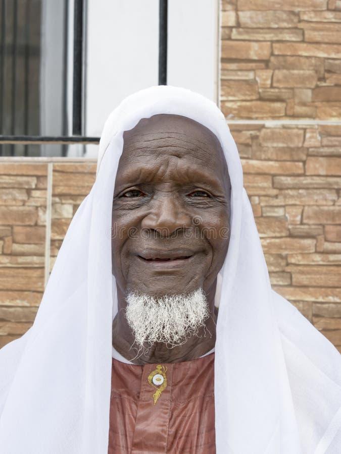 Achtzigjähriger afrikanischer Mann, der in der Straße lächelt lizenzfreies stockfoto