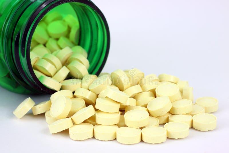 Acide folique débordant la bouteille de pillule verte image libre de droits