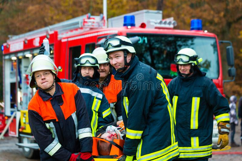 Acidente - corpo dos bombeiros, vítima do acidente na maca fotos de stock royalty free