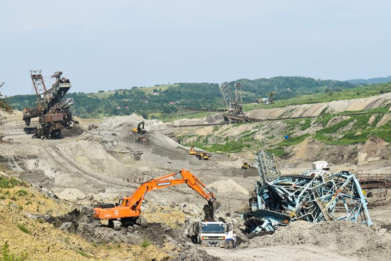 Acidente da mina de carvão com uma máquina pesada da extração dentro da exploração de carvão A máquina escavadora enorme desmoron imagem de stock