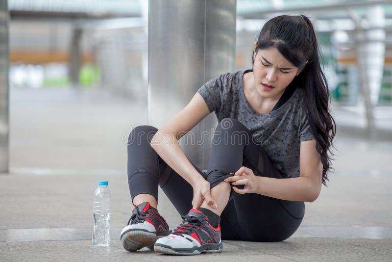 acidente de corrida do pé de ferimento da jovem mulher asiática da aptidão do exercício que exercita na rua na cidade urbana asse foto de stock royalty free
