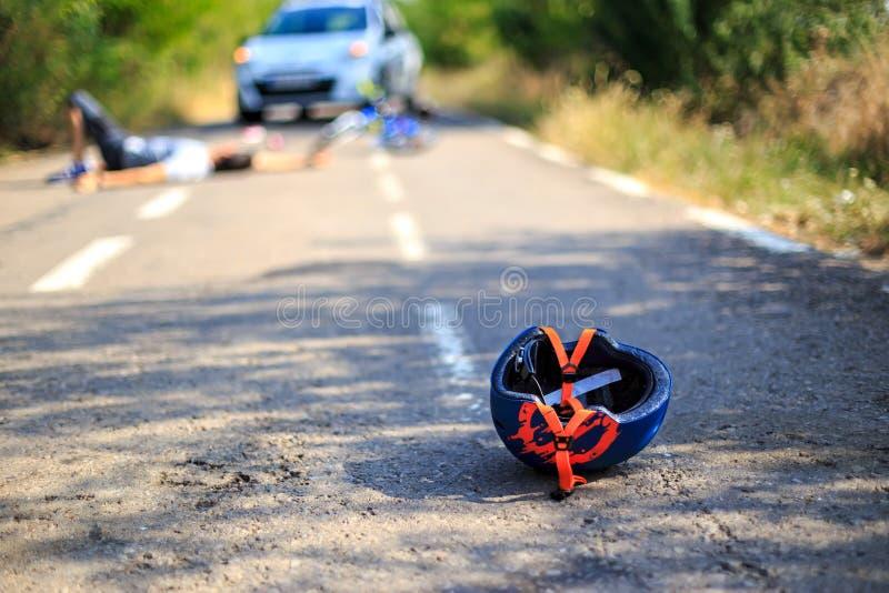 Acidente de viação com o capacete ferido da pessoa e da bicicleta na estrada fotografia de stock