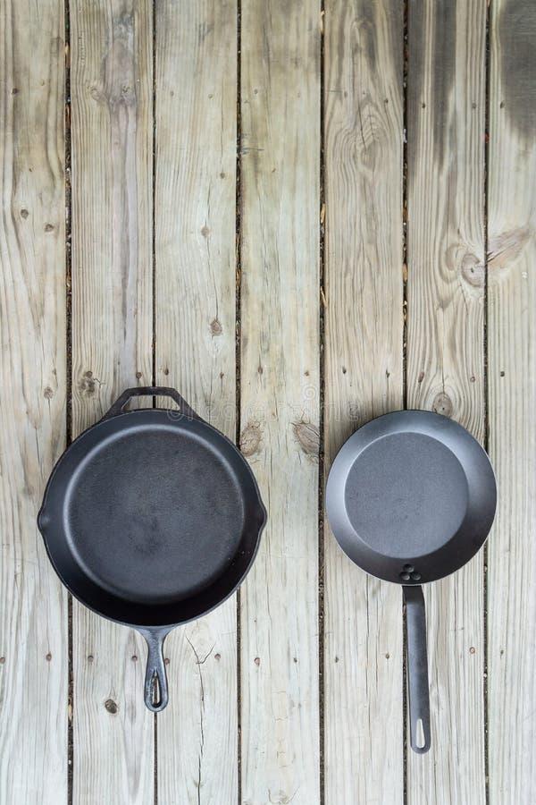 Acier au carbone contre la fonte contre les casseroles de téflon et les poêles - l'espace de copie sur le dessus photographie stock