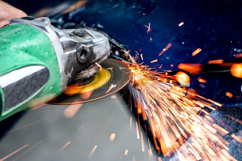 Acier de coupe de travailleur d'industrie lourde avec la broyeur d'angle photo stock