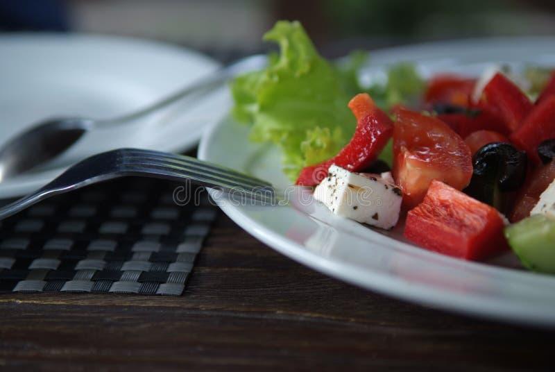 Acima da foto próxima de uma salada grega com a forquilha rústica fotografia de stock