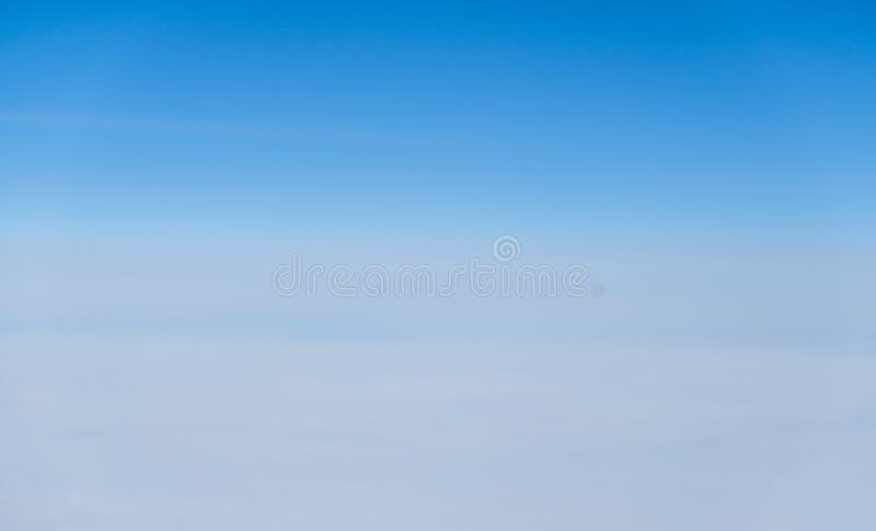 Acima da vista muitas nuvens pequenas no céu azul do avião imagem de stock