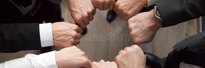 Acima do grupo horizontal da vista os empresários puseram os punhos na forma do círculo foto de stock royalty free