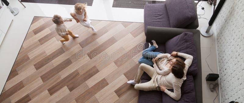 Acima dos pais da vista que descansam nas crianças do sofá que correm o jogo junto imagem de stock