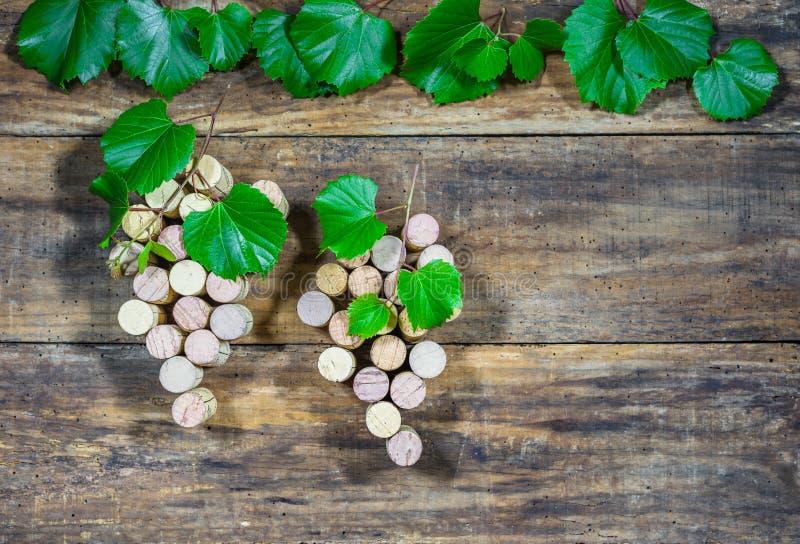 Acini d'uva dei sugheri del vino sui bordi di legno marroni rustici immagini stock