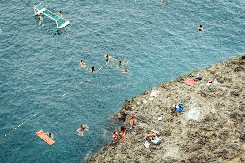 Acitrezza,卡塔尼亚,西西里岛,意大利–威严08日2018年:人浴在独眼巨人的岩石的附近海 免版税库存照片