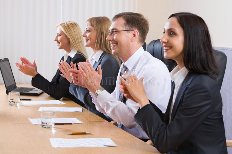 Acknowledgement. Portrait of successful applauding young people sitting in line in black comfortable chairs at the table with monitor, papers and glasses of stock photography