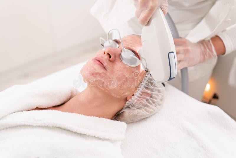 Acné anti phototherapy con el equipo profesional Mujer hermosa en salón de belleza durante procedimiento del rejuvenecimiento de  fotos de archivo