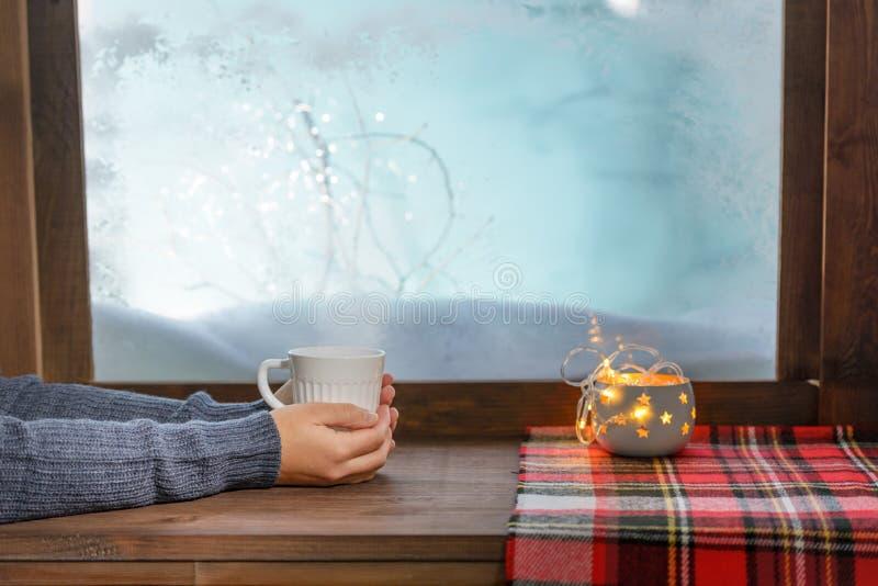 Acogedor ventanal con taza de té y manta caliente imagenes de archivo