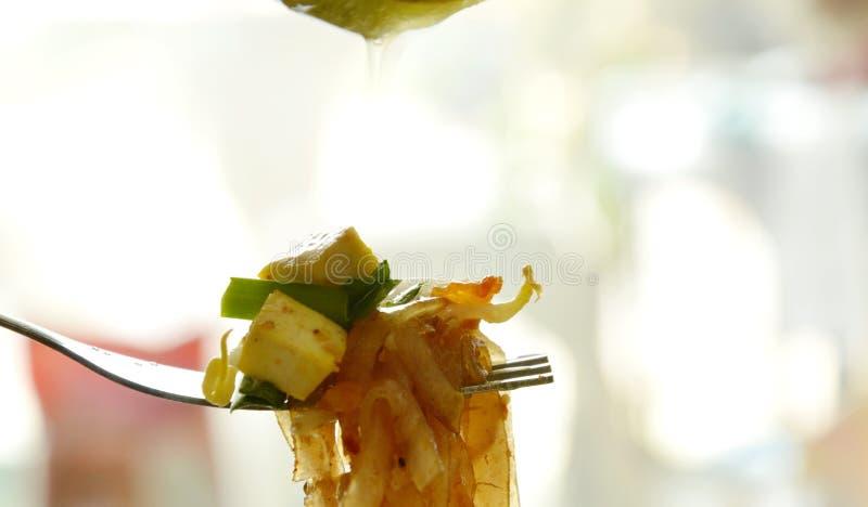 Acolchoe agitação tailandesa macarronetes de arroz finos fritados na forquilha e no cal deixando cair do limão foto de stock