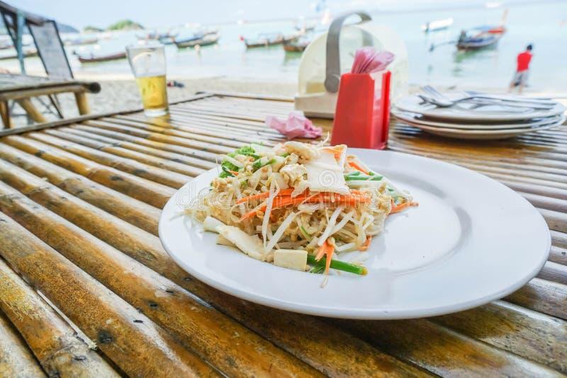 Acolchoe tailandês no prato branco no restaurante exterior na praia foto de stock