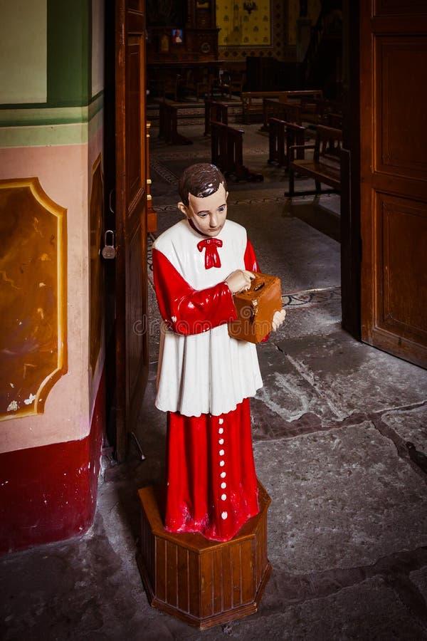 Acolyte med donationsbox för gåvor i kyrkan arkivbild