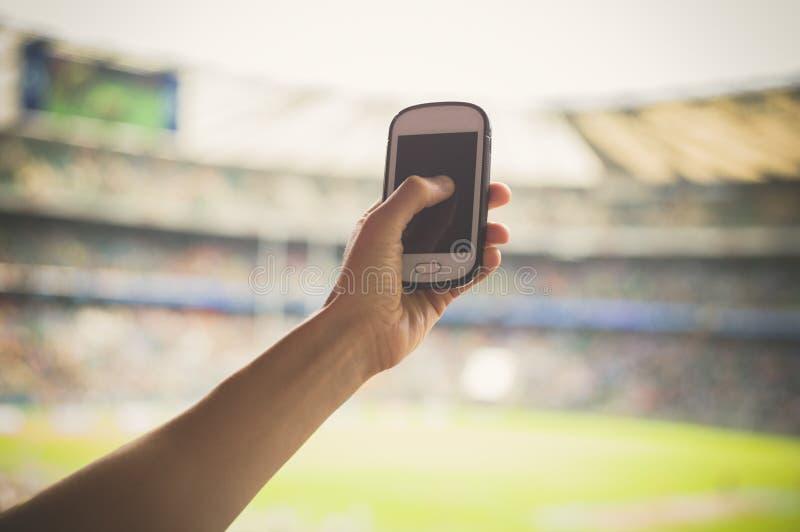 Acontecimiento deportivo de la película de la mano en el teléfono fotografía de archivo libre de regalías