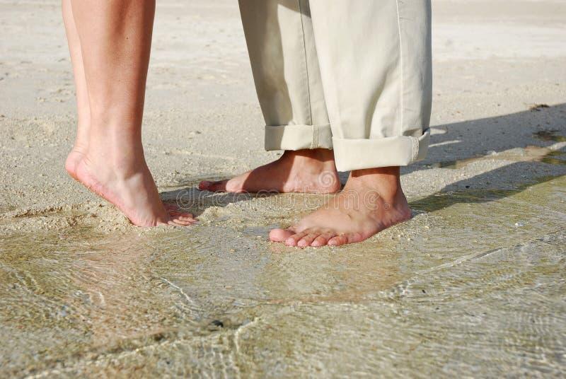 Acopla os pés que estão na praia imagens de stock