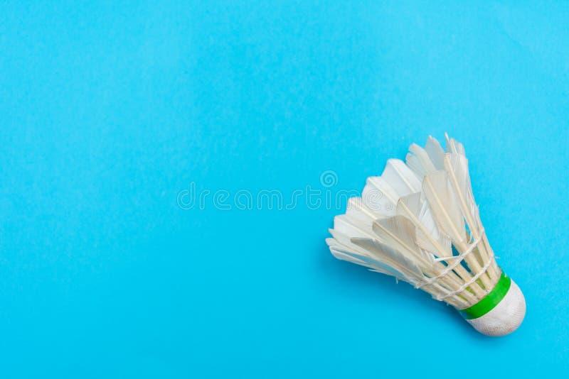Acoplamento de Badminton ou birdie sobre um fundo plano azul brilhante sólido que simboliza esportes e atividade com espaço de có fotos de stock royalty free