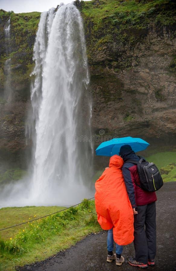 Acople a admiração da cachoeira de Seljalandsfoss em um dia chuvoso Seljalandsfoss foto de stock royalty free