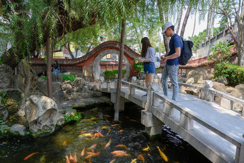 Acople a alimentação do Kois na lagoa do jardim chinês com porta da entrada ao templo de Chikhan, Tainan, Taiwan imagem de stock royalty free