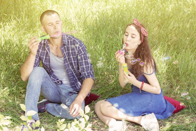 Acople amantes fundem bolhas os amigos riem o menino e a menina do piquenique do verão estão sentando-se na grama imagens de stock royalty free