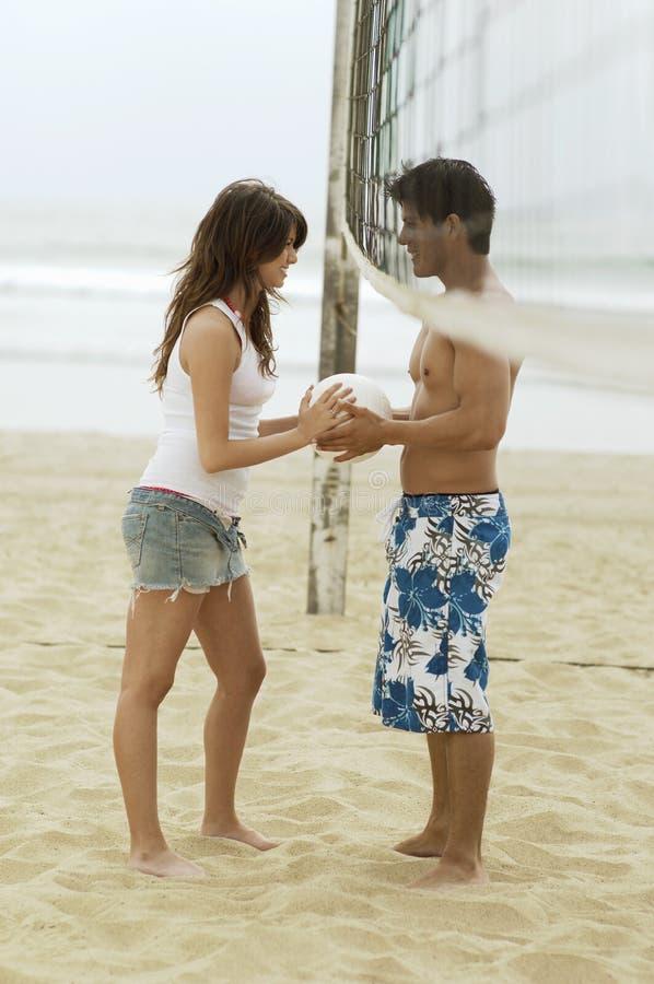 Acople ambo o voleibol da terra arrendada sob a rede na praia imagens de stock
