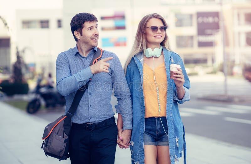 Acople a apreciação de um dia para fora na cidade após o escritório Homem novo e mulher que dão uma volta através das ruas e que  foto de stock