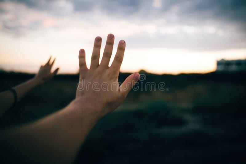 Acople as mãos no fundo do céu arenoso bonito do penhasco e do por do sol Praia de exploração dos pares na ilha tropical na baía  imagem de stock