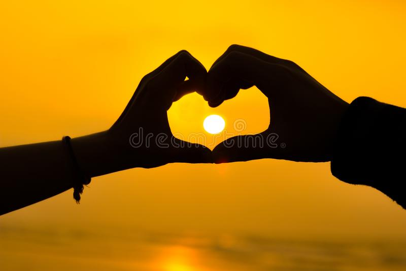 Acople as mãos que fazem um coração para amar o sillhoute do sinal durante o nascer do sol em uma praia fotografia de stock royalty free