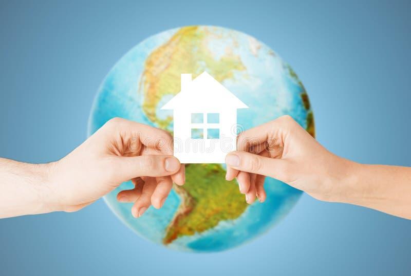 Acople as mãos que guardam a casa verde sobre o globo da terra imagens de stock royalty free