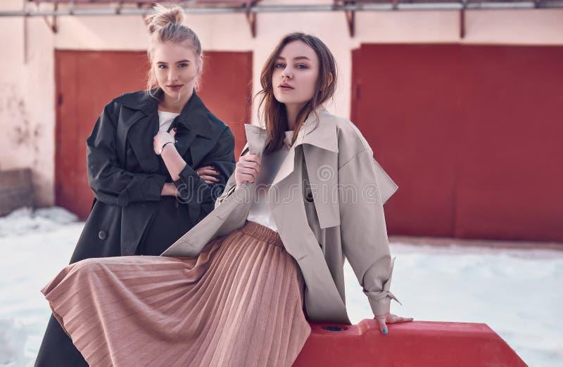 Acople as meninas bonitas do moderno que vestem revestimentos longos da forma na rua imagem de stock