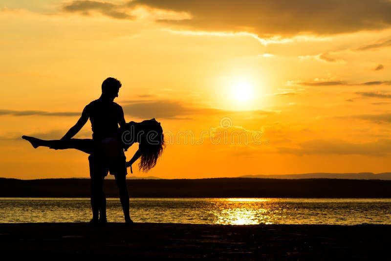 Acople as silhuetas que guardam no por do sol pelo mar, dançando fotografia de stock royalty free