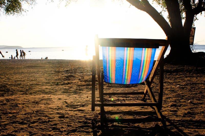 Acople a cadeira de praia na praia com fundo do céu do por do sol imagens de stock