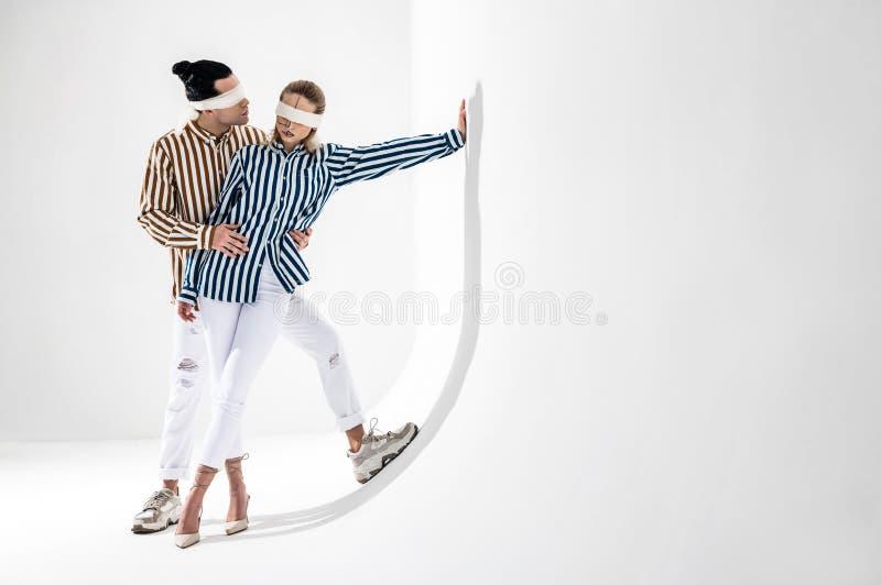 Acople a calças branca vestindo e as camisas listradas que levantam junto fotos de stock royalty free