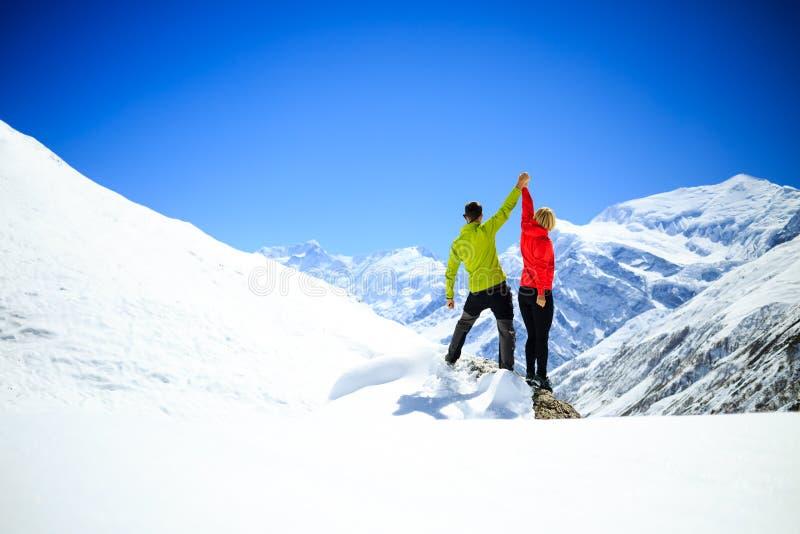 Acople a caminhada do sucesso do homem e da mulher em montanhas do inverno imagem de stock