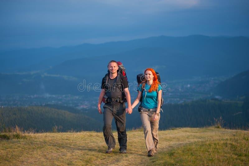 Acople caminhantes com as trouxas que guardam as mãos, andando nas montanhas imagem de stock