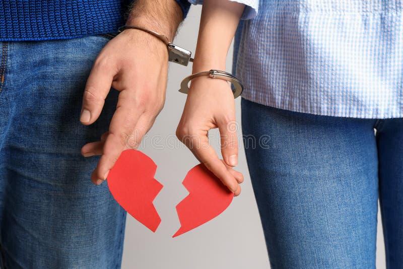 Acople com algemado junto entrega guardar coração quebrado no fundo claro Conceito do apego imagens de stock