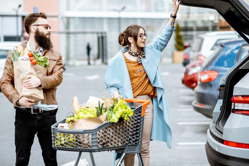 Acople com sacos de compras e alimento fora foto de stock