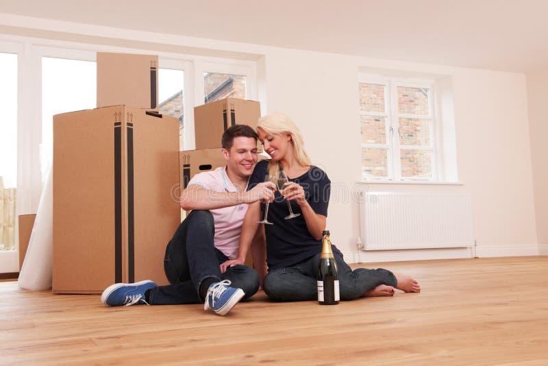 Acople a comemoração de mover-se na casa nova com Champagne imagens de stock