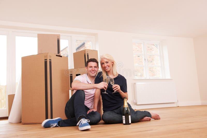 Acople a comemoração de mover-se na casa nova com Champagne imagem de stock