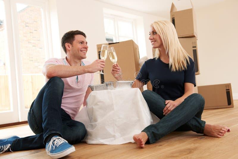Acople a comemoração de mover-se na casa nova com Champagne And Takea fotografia de stock