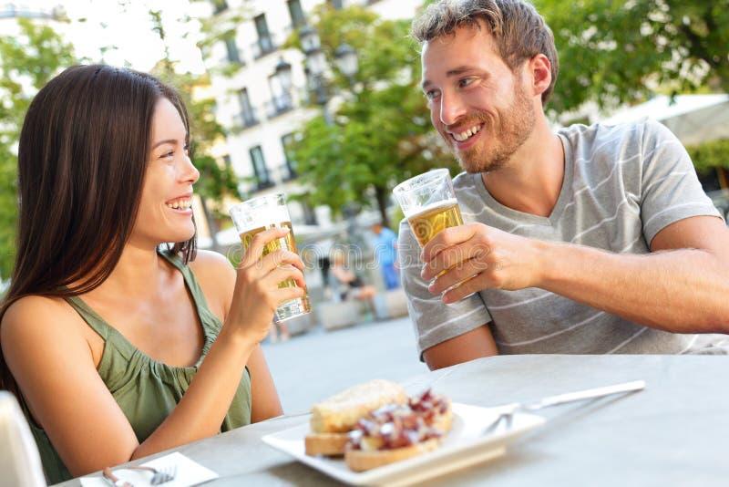 Acople comer os tapas que bebem a cerveja na Espanha do Madri imagem de stock royalty free