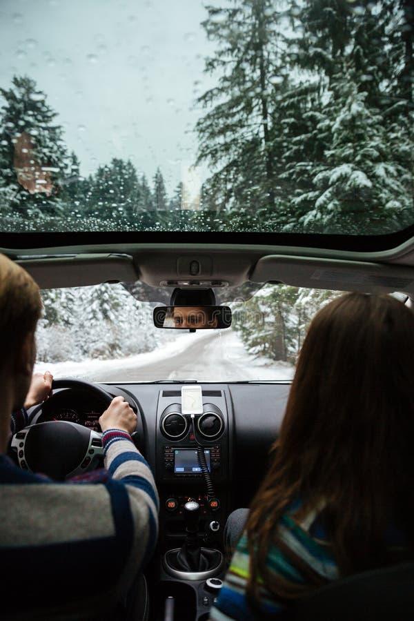 Acople a condução no carro moderno na floresta do inverno foto de stock royalty free