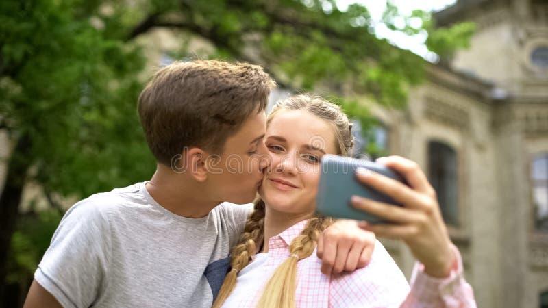 Acople dos adolescentes que fazem o selfie, menino que beija a menina, foto para o blogue pessoal, amor fotos de stock