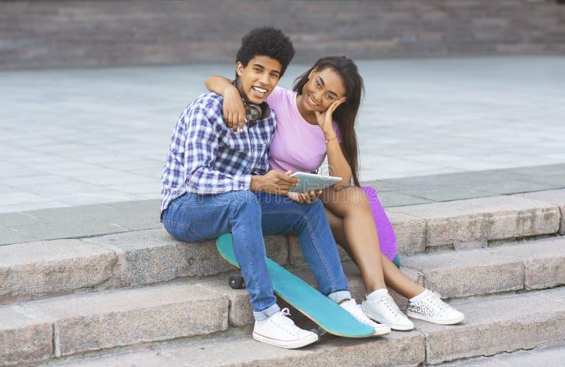 Acople dos adolescentes que sentam-se em escadas com tabuleta digital fotografia de stock