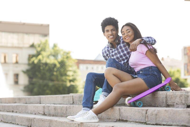 Acople dos adolescentes que sentam-se nas escadas que levantam à câmera foto de stock royalty free