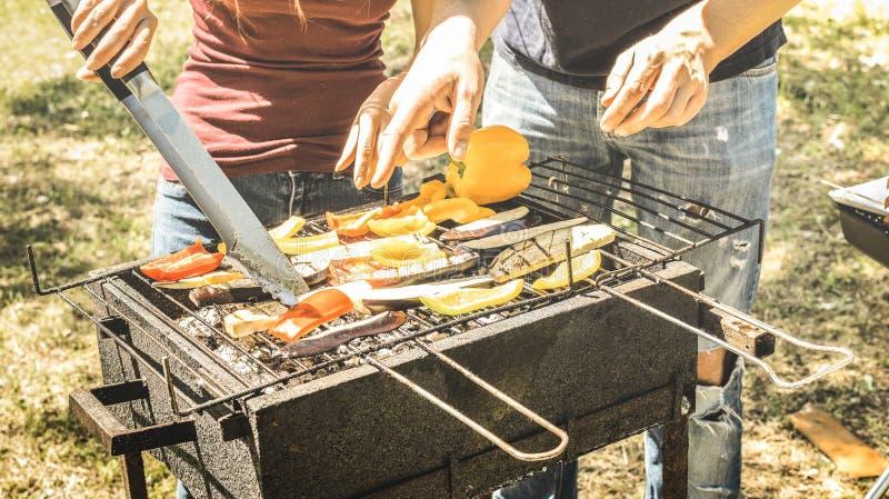 Acople dos amigos que cozinham vegetais no assado - as beringelas e as pimentas cozinhadas na grade no partido de jardim do BBQ - imagem de stock