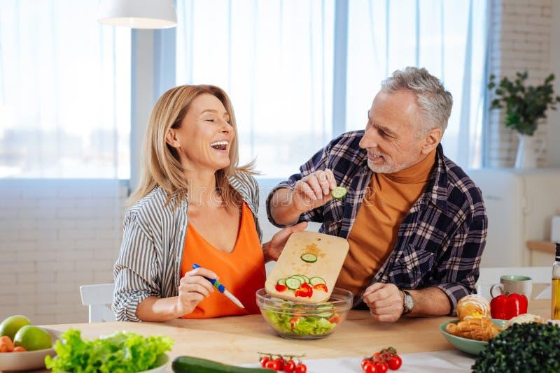 Acople dos homens de negócios que sentem alegres ao cozinhar junto fotografia de stock royalty free